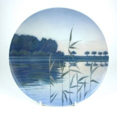 Two Royal Copenhagen wall plates, circa 1894 - 1922. Two Royal Copenhagen wall plates, circa 1894 - 1922. One plate depicting a scene by a lake with water rushes in the foreground, marked beneath with the green Royal Copenhagen stamp, three wavy lines in blue and numbered 1302/1122, the other decorated with a still life of hanging fruit berries, marked beneath with the green Royal Copenhagen Denmark stamp, three wavy lines in blue and numbered 1091/1125. (2 items) 9.1 in (23 cm) diameter…