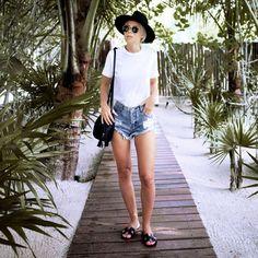 Look da blogueira Victoria Törnegren no verão: t-shirt branca + shorts jeans + chapéu preto.