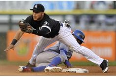 Chicago White Sox second baseman Carlos Sanchez makes the catch but Toronto's Jose Reyes slides through his legs to steal a base in the first inning.