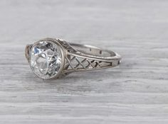 Antique Edwardian engagement ring collet-set with anold European-cut diamond weighing 1.30 carat with GIA certificate stating the diamond is F color/VS2 clarity. In a lattice work platinum mount. Circa 1914 Stunning hand work of the platinum setting makes this ring especially distinct. The low profile Edwardian setting makes it very wearable. Learn about Edwardian era engagement rings. Diamond and gold mining has caused devastation in areas such as Africa, wreaking havoc on delicate…