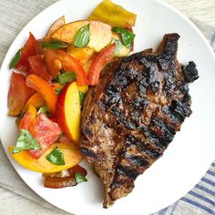 When you've got peaches and tomatoes, who needs lettuce? Get the Recipe: Grilled Pork Chops with Heirloom Tomato and Peach Salad   - Delish.com