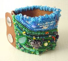 Take this beautiful garden anywhere you go. This bead embroidered cuff is art you can wear. This cuff is made using a technique called bead embroidery. Each tiny bead is hand sewn onto fabric to create a one of a kind piece. Made using small glass beads and cat eye cabochons and accented with little pewter charms and glass flower beads. It is then all hand sewn onto a piece of light brown leather and finished with two silver snaps.  The beadwork measures 2 3/8 inches (6.032 cm) by 6 3&#x...