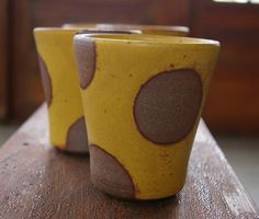 Wheel thrown tumbler, sunshine yellow glaze. Polka dots were made using a wax resist technique. Perfect for any hot or cold liquid. Microwave and dishwasher safe. Holds 8 ounces, measures approximately 4 tall, 3.5 diameter. This listing is ready to ship. About Lemonbee Pottery:  All pieces are made using a brown stoneware and fired in a cone 10 reduction kiln. Clay and glazes are always lead free and food safe. My goal is to make handmade wares that you can use and enjoy everyday! Since each…