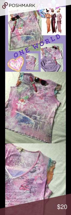 """{ONE WORLD}-- pretty pastel top  Gorgeous lavenders , pinks, purple...well u get the pic!  this was put on for an hour..n washed..never wore it, too small for me!has the prettiest sheer capped sleeves!  bust : 20"""" LF ...length: 24""""  v-neck has lavender studs on left side top on flower!! match up with the lavender pants shown ( pants listed separately, or I can give better price together I SHIP SAME DAY WITH A GIFT!  TY ONE WORLD Tops Tees - Short Sleeve"""