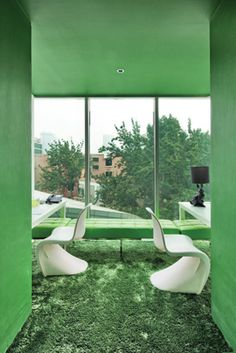 Green walls, carpets and bench seating inside one of the meeting rooms of Woods Bagot's Beijing studio.