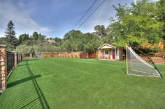 Backyard with two large play areas with artificial turf -  sports court and sports field.