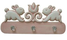 Bunnies Coat Rack in Multiple Colors by Marie Ricci. $150.00. Theme: Bunnies. Primary Color: Custom. Usually Ships within 2 Weeks10in x 20inThis precious Bunnies Coat Rack is a hand-painted peg rack with cute bunnies up top. A keyhole mount and faceted knobs are included, mounting pattern included as well. Available in 18 different colors and in a solid or distressed finish, this piece will be a great accessory for your child's bedroom or nursery. Please note that the soli...