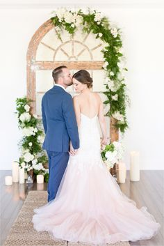 Blush wedding dress with blue suit with romantic ceremony arch