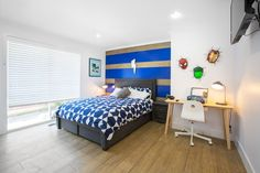 Electric blue and timber feature wall in this heroes themed kids bedroom!