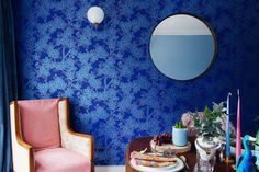 Great cozy nook with an vintage armchair, a beautiful blue wall, a round mirror and a wooden table.  Check out our website to find more inspiration!
