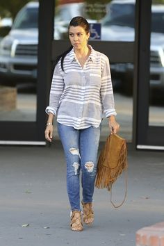 Kourtney Kardashian wears a striped button-down shirt, distressed skinny jeans, lace-up heels, and a fringe suede bag