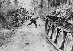 American soldiers crossing a dirt road as Germans shoot at them. Normandy, France, 25 July, 1944.