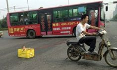 That is NOT a good idea  -  Police in China are hunting a motorcyclist who was pulling his son behind him in a drinks crate.  The tot - clearly too young to ride pillion - stares out from the box trustingly as he is towed along the road by a piece of rope. The scene was caught by a passer-by in Xi'an, Shaanxi province, who posted it on social networking websites.