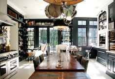 LOVE the table in the middle of the kitchen. Also the black and white contrast. Beautiful.
