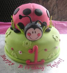 Green first birthday cake with ladybug on top