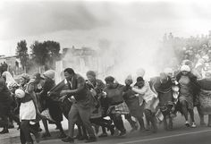 1977 - Police throw tear-gas at a group of chanting residents of the Modderdam squatter camp protesting against the demolition of their homes outside Cape Town. (Leslie Hammond)