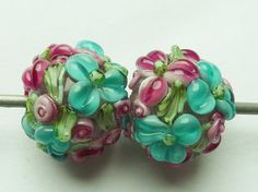 Glass lampwork bead set in light pink with raised flower decoration.