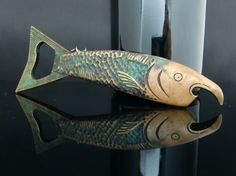 Rare collectible bar tool combining a corkscrew and a two different cap lifters, made in the form of a fish. Made of brass, with verdigris