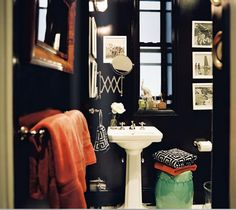 Dramatic bathroom.  Love the pop of orange towels and the green garden stool.
