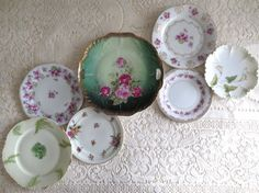 This is a stunning mix of 7 mismatched vintage and antique floral plates perfect for a wall collage. These plates feature shades of purple, pink, and green. They range in size from 6 inches to 9 inches in diameter. Make a beautiful wall display or use them for a special event. Very cottage shabby chic or perfect for a cottage kitchen. These are in good condition without any chips, cracks or crazing. There is some fading and paint loss to the green center plate. Backstamps include: -Noritake…