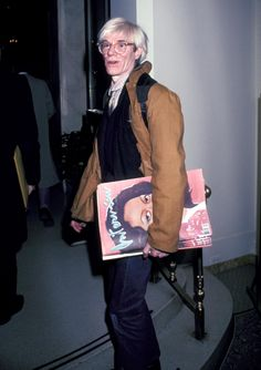 Holding a copy of Interview magazine, Andy Warhol arrives at a Carolina Herrera fashion show in 1981. Warhol founded the magazine in 1969.
