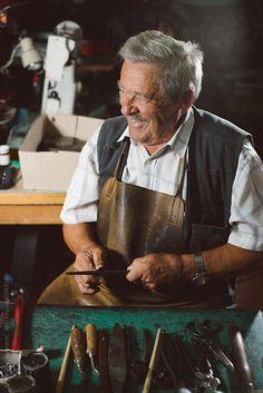 Smiling shoemaker working at his desk by BrkatiKrokodil | Stocksy United