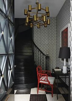 For the foyer of a penthouse apartment in Toulouse, France, Suduca & Mérillou chose a black and white palette with a flash of red in the form of a Maison Jansen chair. The space also includes a 1960s brass chandelier and a glass table lamp by Madeleine Castaing.