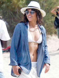 We love Michelle Rodriguez's beach style—just check out her white bikini, fun fedora, denim top and sunnies with flash lenses!