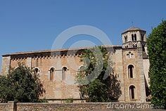 Photo made in Girona in Spain. The picture shows the side of a simple church in the city. The photo was taken from the outside of the low brick low wall surrounding the church and within which stand of small trees.