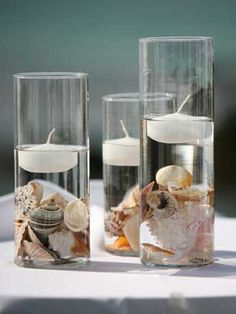 Seashells in vases with floating candles.