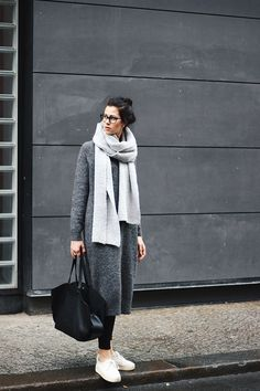 Elisa from the Fashion- and Lifestyleblog www.schwarzersamt.com shows a minimalistic autumn winter look in grey. She is wearing a woolen longdress from ASOS, a xxl scarf in light grey from ASOS, white platform sneaker from H&M and a black ZARA daily bag. It's a cozy and minimal grey outfit with white and black details.