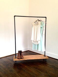 The Logan Square Garment Rack is the hippest way to display and store clothes, shoes and accessories. Reclaimed wood bottom with black iron pipe frame.