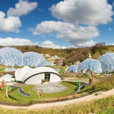 A wide shot of the Eden Project on a sunny day showing the biomes and stage area