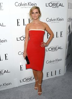 Reese wore a red strapless Calvin Klein dress with a thin white band along the top. This dress fits Reese like a glove! I like the color with the white band and how it matches her white sandals! The shiny box clutch pulls it altogether!