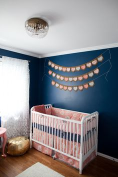 Bold, navy walls in a nursery - love the look, especially paired with fun corals, pinks and golds!