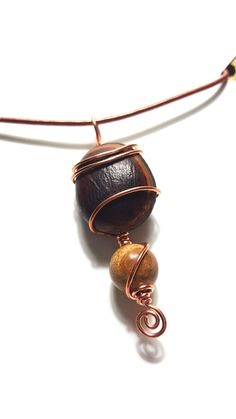 The top bead  is called  Hamburger Sea Bean..I found it on the beach in Cocoa Beach,  Florida and from my research it appears to have floated on the ocean waves from Ecuador or Peru...Cool Beans!!!  The bottom bead is a 12mm Picture Jasper bead.  They are wrapped in copper wire and are on an 18 inch copper colored cord with lobster clasp.  Pendant is approximately 2.25 inches long.  This is a one of a kind item as are all of my jewelry pieces. | Shop this product here…