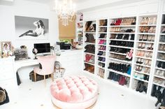 Incredible closet with white walls, white floors with gold inlay detail and velvet pink tufted ottoman and chair. Wall to wall shoe storage, crystal chandelier and black and white photography.