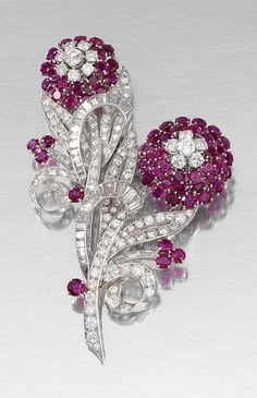 RUBY AND DIAMOND DOUBLE CLIP BROOCH, 1950S.  Each designed as a flower, the stems and leaves set with circular-cut and baguette diamonds, each flower head and bud set with circular-cut rubies, detachable frame numbered.