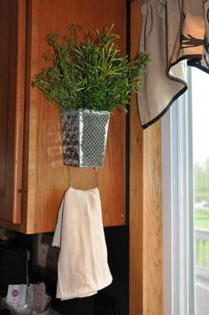 Turn an old cheese grater upside down and add a small plant to the inside and a tea towel on the handle.
