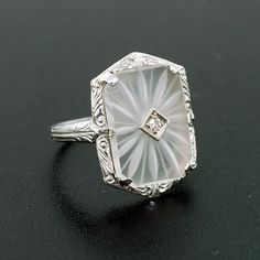 A simply beautiful rock quartz crystal and diamond ring from the Art Deco period (ca1920) Set in a 10kt white gold setting, the ring is comprised of an octagonal rock quartz crystal plaque with a single diamond set in the center.