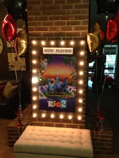"""DIY """"now playing"""" sign for kids movie night party. Any sign spray painted black cut holes evenly along border. Use the string lights (can buy at target) unscrew and then screw back into holes- be careful not to squeeze too hard, they easily break. And buy movie poster for the movie you are playing."""