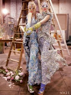 Caroline Trentini and Lily Donaldson dancing in a painting studio, wearing masks. Trentini (left) is wearing a long, floral dress by Gucci. Donaldson (right) is wearing a long, St-Tropez-print ruffled dress by Roberto Cavalli. Both models are wearing gold python wedges by Prada, opera gloves by Daniel Storto with bracelets by Tom Binns.