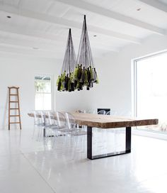 diy wine bottle chandelier, reclaimed wood table with metal strap legs and ghost chairs. minimalist design all white room makes the furniture the star Diy Bottle Lamp, Wine Bottle Chandelier, Diy Chandelier, Pendant Lamps, Chandelier Creative, Pendant Lights, Pendants, Lighted Wine Bottles, Bottle Lights