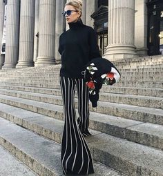 Striped black and white pants with black turtleneck sweater.