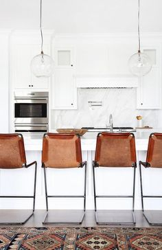 """Leather backed bar stools line up at the marble breakfast counter in this bright, modern, all-white kitchen for a touch of rustic modernism. Read more from """"Home Tour: A Modern Bohemian Family Abode"""" on  MyDomaine."""