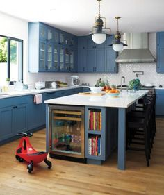 A sunny kitchen can handle moody blue cabinets and still be cheery, especially with gleaming white counters that bounce light around.