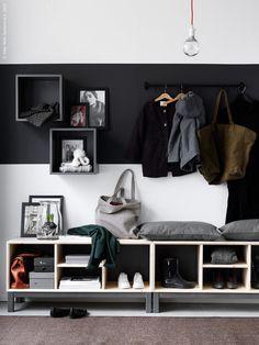 Skapa en personlig hall med bilder med svarta ramar NYTTJA i olika storlekar. NORNÄS bänk med förvaringsfack, VALJE väggskåp mörkgrå, FINTORP stång svart, FINTORP krok svart. OSTED mattabrun, lampa SEKOND upphäng röd, NITTIO LED glob.