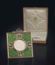 PROPERTY FROM THE ROYAL HOUSE OF SAXE-COBURG-GOTHA: A TWO-COLOUR GOLD-MOUNTED ENAMEL AND NEPHRITE PHOTOGRAPH FRAME BY FABERGÉ, WORKMASTER MICHAEL PERCHIN, ST PETERSBURG, CIRCA 1890. Square, the nephrite body with gold mounts, enamelled with alternating red and white bead and reel pattern, centring a similarly decorated circular aperture, applied with four ribbon-tied and laurel-entwined thyrsi, surmounted by a gold ribbon crest.