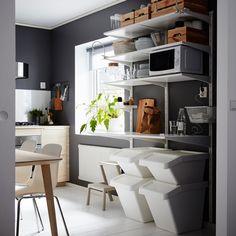 Темно-серая кухня с белыми настенными полками икорзинами для сортировки мусора внизу.