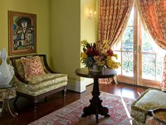 A special resting place was created in a second floor hallway that leads to an outdoor balcony overlooking this Houston estate. Oversized chairs, a wood pedestal center table, brass side tables and abstract artwork are complimented by the antique wool area rug and custom draperies in a fuchsia pink Ikat print hung on a hand forged iron rod.